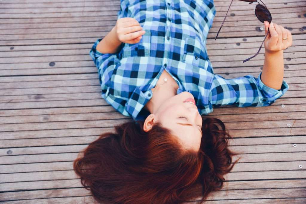 girl in flannel shirt lying on a dock