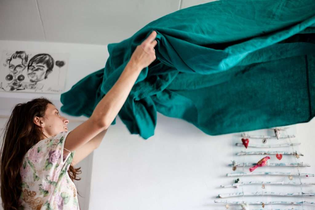 a woman putting bed sheets on a bed